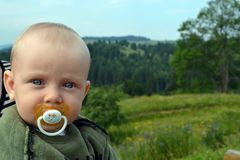 Blue-eyed baby with a pacifier outdoor royalty free stock photo