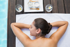 Tranquil brunette lying on towel poolside with beauty treatments. Outside at the spa Royalty Free Stock Images