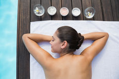 Tranquil brunette lying on towel poolside with beauty treatments Royalty Free Stock Photo