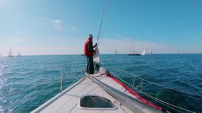 Skipper or sailor stands on deck nose of yacht stock video