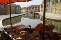 Tranquil canal in Comacchio. View of a tranquil canal, lined by old houses, seen through a streetside stall. Picture of the famous Italian city of Comacchio Royalty Free Stock Image