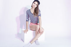 Tranquil Caucasian Fashionable Brunette in Hat and Striped Shirt Posing in Studio Against White. Royalty Free Stock Images