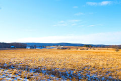 Tranquil countryside landscape in West Virginia. The snow is melting on the fields with a picturesque background of forest trees and farmhouses Royalty Free Stock Photo