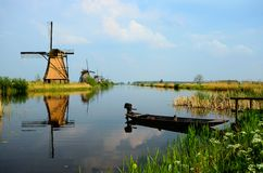 Tranquil Dutch countryside. Historic windmills along the canals at Kinderdijk with boat, Netherlands Royalty Free Stock Images