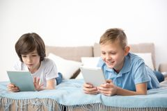 Quite boys relaxing with gadgets. Tranquil kids recreating in living room. They are concentrating on their tablet screens Royalty Free Stock Photos