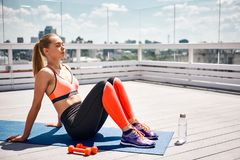 Tranquil lady is relaxing after work out on terrace stock photos