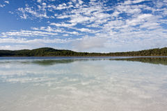 Tranquil Lake. Lake McKanzie in Fraser Island and beautiful blue sky with some nice white clouds royalty free stock photo