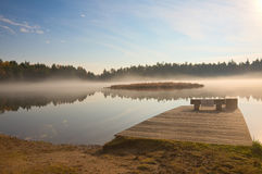 A Tranquil Lake in the Adirondack Park. A tranquil scene at sunrise as the mist begins to rise off the lake Stock Photo
