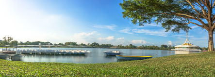 The tranquil lake with a boat in the foreground and the Ratchamangkala Pavilion of Suan Luang Rama IX Public Park Bangkok. In a background at afternoon Royalty Free Stock Photography