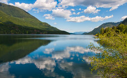 Tranquil Lake With Fluffy Cloud Reflection Stock Photo