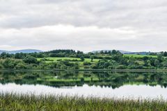 Tranquil Lake in the Irish countryside. This is a picture of a still lake in Irelands countryside. The water is so the it is like a mirror. There are swans stock photos