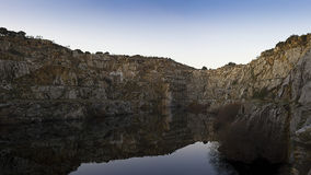 Tranquil lake or quarry. Background landscape of a tranquil lake or quarry ringed with rocky cliffs reflecting the rocks Royalty Free Stock Photos
