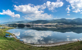 Tranquil lake reflecting the clouds and blue sky. Tranquil lake reflecting the fluffy white clouds and blue sky with a shoreline in the foreground and town Royalty Free Stock Photos