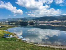 Tranquil lake reflecting the clouds and blue sky. Tranquil lake reflecting the fluffy white clouds and blue sky with a shoreline in the foreground and town Stock Images