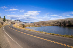 Tranquil Lake Between Road and Hills Royalty Free Stock Images
