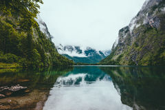 Tranquil lake surrounded by mountain in the foggy weather Stock Photography