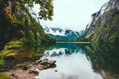 Tranquil lake surrounded by mountain in the foggy weather Royalty Free Stock Images