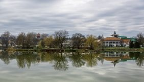 Tranquil landscape with lake, houses, cloudy sky, and trees reflected symmetrically in the water. Nyiregyhaza, Hungary. Beautiful lake with mirror reflections in Stock Image