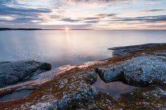 Sunrise on lake with stony coast landscape Royalty Free Stock Photo