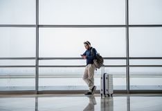 Calm male traveler going abroad. Tranquil man flying abroad on weekend. He is listening to music while waiting for the plane in departure lounge. Copy space in Stock Photography