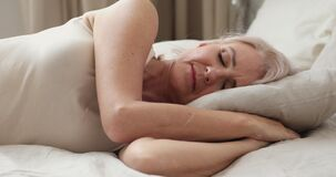 Calm peaceful happy adult older woman sleeping at home.