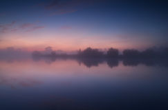 Tranquil misty sunrise on lake Royalty Free Stock Images