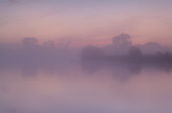 Tranquil misty sunrise over lake Stock Images