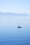 Tranquil morning sea with a sailing ship Stock Photography