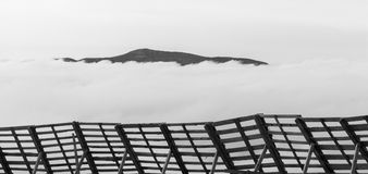 A tranquil mountain scene with clouds cover and fence on a hill. Black and white Royalty Free Stock Photos
