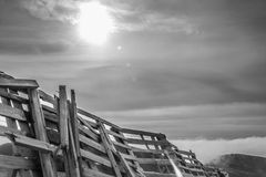 A tranquil mountain scene with clouds cover and fence on a hill. Black and white royalty free stock photo