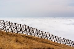 A tranquil mountain scene with clouds cover and fence on a hill. Pastel colors sky in the background Royalty Free Stock Photos