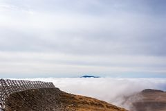 A tranquil mountain scene with clouds cover and fence on a hill. Pastel colors sky in the background Royalty Free Stock Images