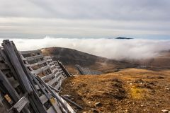 A tranquil mountain scene with clouds cover and fence on a hill. Royalty Free Stock Photos