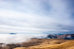 A tranquil mountain scene with clouds cover on a hill. Some cabi. Ns in the backgroud Royalty Free Stock Photo