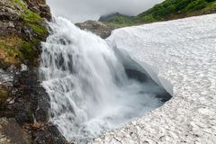 Tranquil mountain waterfall falling into the snowfield. Picturesque mountain waterfall falling into the snowfield and traditional nature of Kamchatka Peninsula Stock Images