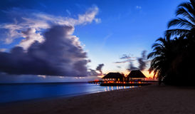 Tranquil night over beach resort. Exotic nature of Maldives, scenic destination, luxury bungalow and restaurant on seashore Stock Image