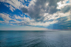 Tranquil ocean water and blue cloudy sky. Royalty Free Stock Images