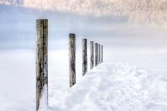 Tranquil perspective view on a snowy mountain lake. Serene scene of row of wooden poles of a mountain lake levee, in perspective. Everything is covered in snow Stock Image