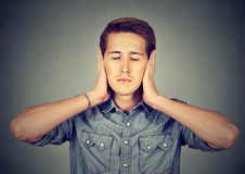 Tranquil, relaxed young man covering ears, eyes closed Stock Image