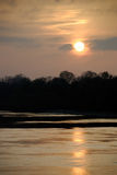 Tranquil river in the twilight. Reflect sun Stock Photos