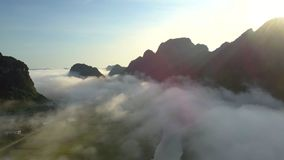 Tranquil river in valley covered with fog against hills stock video