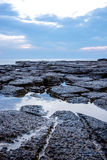 Tranquil rock pool on a rocky shoreline Stock Photography