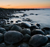 Tranquil rocky coast. Large boulders being washed by waves lit by the orange sky Stock Photos