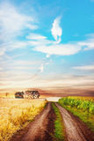Tranquil rural scene with road between two fields. Royalty Free Stock Images