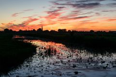Deep red and orange sky with reflections in the water of a canal near Gouda, The Netherlands royalty free stock photos