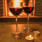 Two glasses of red wine and candles near cozy fireplace, in country house, winter vacation, horizontal. Tranquil scene before cozy fireplace, with two glasses of stock photos
