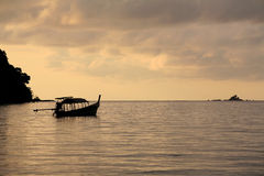 Tranquil scene of long-tailed boat on sea at dawn royalty free stock photo