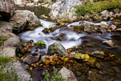 Clear mountain river with small waterfall. Tranquil scene with a mountain river and waterfalls, dotted with fall foliage Stock Photography