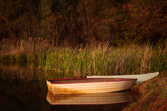 Tranquil scene of a small red and white fishing bo Stock Photography