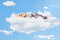 Tranquil scene of a woman sleeping on cloud. Tranquil scene of a young woman dreaming and sleeping on a cloud up in the sky royalty free stock image